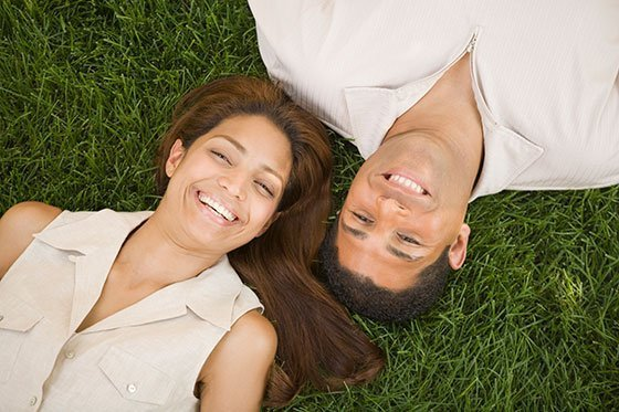 happy couple laying on green grass