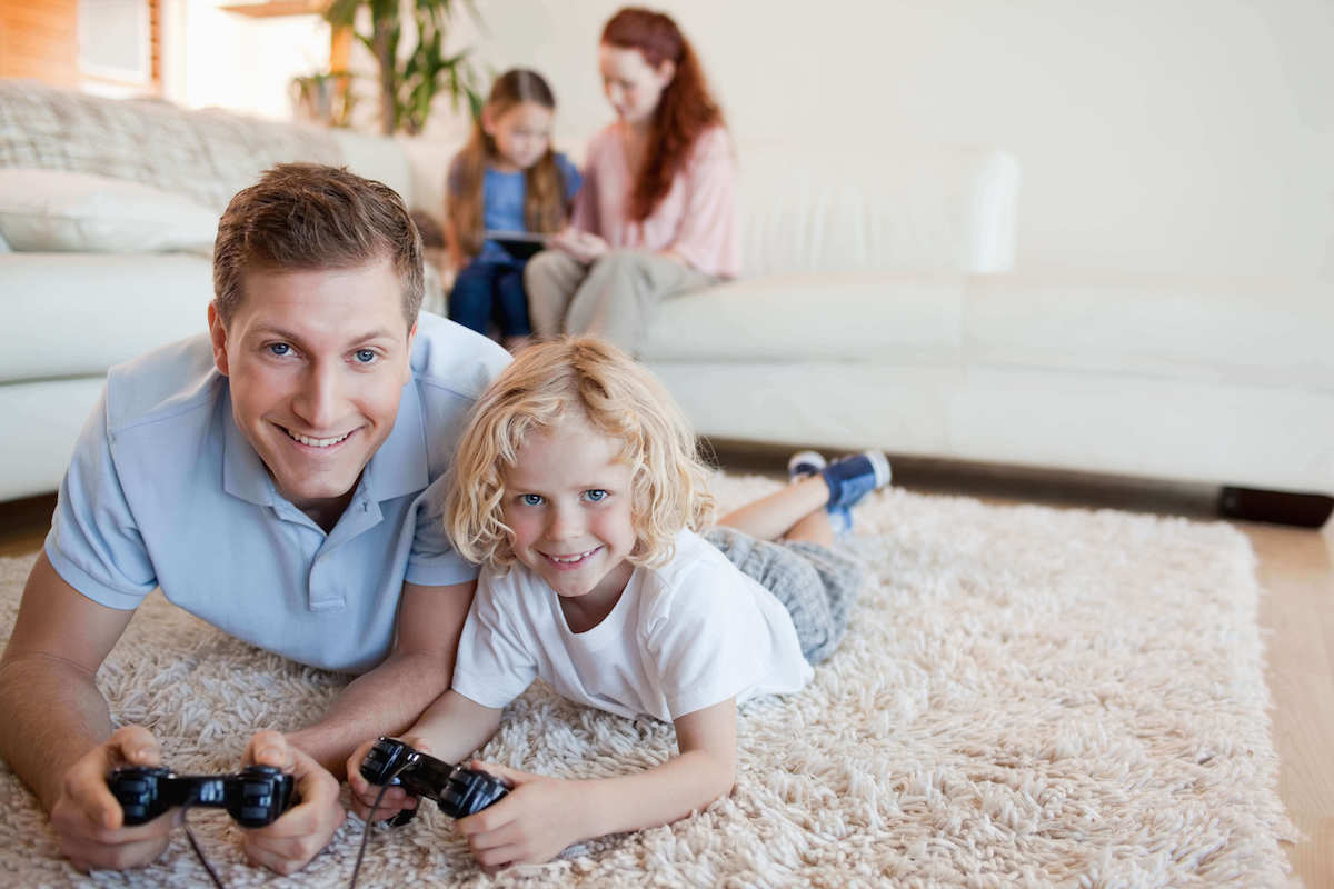 father and son playing video games on a clean carpet