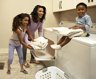 family hanging out around washer and dryer